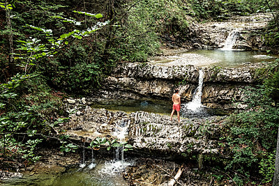 Germany, Upper Bavaria, Bavarian Prealps, lake Walchen, young man is standing in a torrent - p300m2083967 von Wilfried Feder