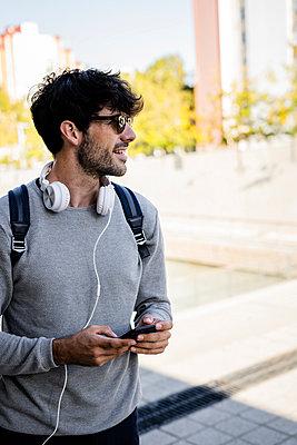 Smiling man holding smartphone in the city - p300m2140423 by Giorgio Fochesato