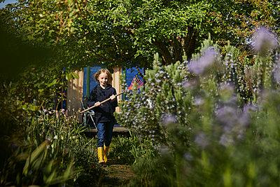 Girl in allotment garden holding a rake - p300m2199238 by Maya Claussen