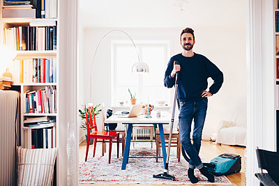 Portrait of happy man standing with vacuum cleaner in dining room at home - p426m1451480 by Maskot