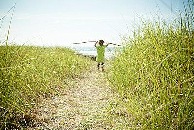 Female toddler carrying long stick - p924m884303f by Robyn Breen Shinn