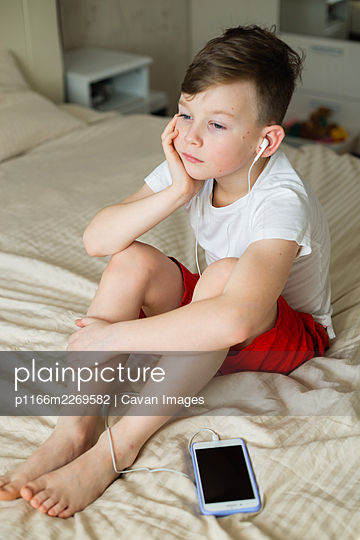 boy listening music with headphones on bed - p1166m2269582 by Cavan Images
