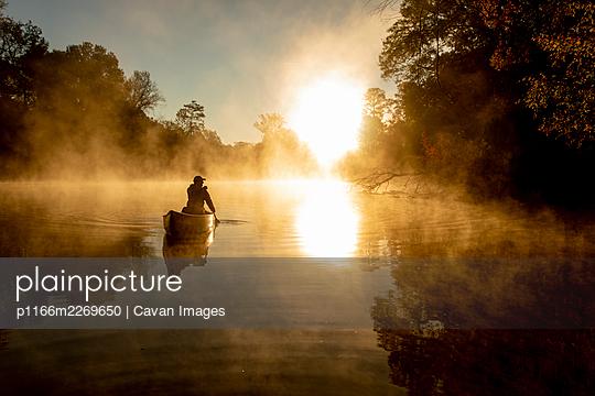 Sunrise canoe ride on foggy river. - p1166m2269650 by Cavan Images