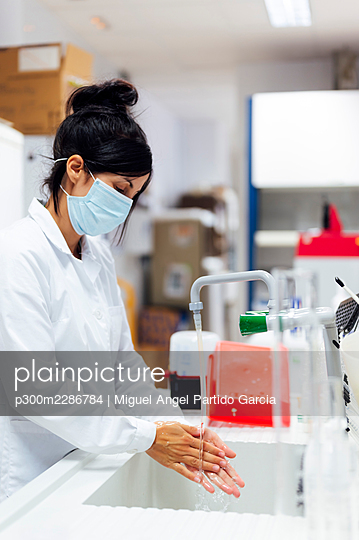 Mature female researcher wearing protective face mask washing hands in laboratory - p300m2286784 by Miguel Angel Partido Garcia