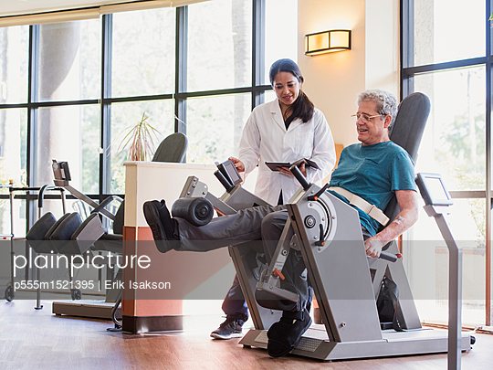 Physical therapist helping man strengthen legs - p555m1521395 by Erik Isakson