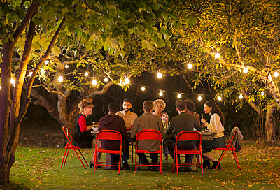 Friends enjoying dinner garden party under trees with fairy lights - p1023m2087960 by Paul Bradbury