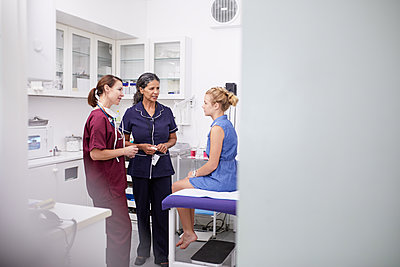 Female doctor and nurse talking to girl patient in clinic examination room - p1023m2088123 by Trevor Adeline