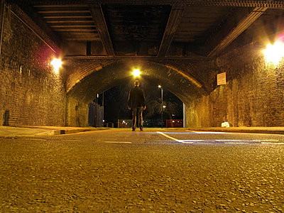 Silhouetted man in road under railway arch  - p1072m829407 by Neville Mountford-Hoare
