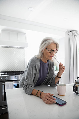 Senior woman drinking coffee and using smart phone in kitchen - p1192m2109763 by Hero Images