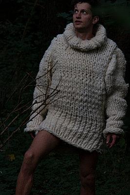 Stehender junger Mann in weißem Wollpullover - p1650m2230888 von Hanna Sachau