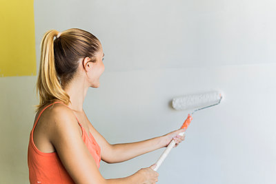 Young woman painting wall at new home - p300m2041790 by Francesco Buttitta