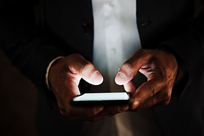 Male entrepreneur using smart phone in dark - p300m2287307 by Eva Blanco