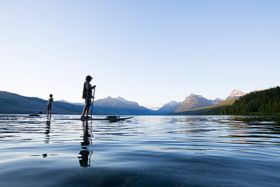 A man and woman stand up paddle boards (SUP) on Lake McDonald in Glacier National Park.  - p343m989313f by Craig Moore