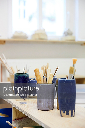 Various paintbrushes in containers on table at workshop - p426m2205121 by Maskot