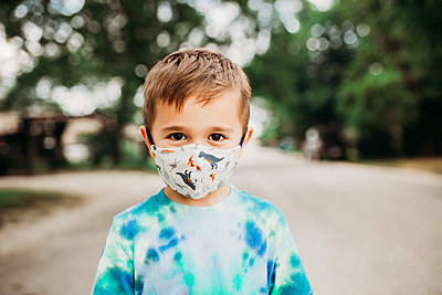 Preschool age boy standing outside wearing homemade fabric mask - p1166m2201634 by Cavan Images