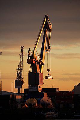 Port crane at sunset - p179m1467415 by Roland Schneider