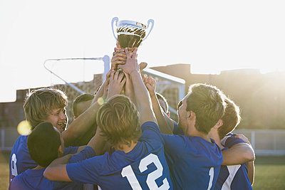 Soccer team lifting trophy together. - p328m840844f by Hero Images