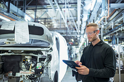 Engineer with digital tablet on production line in car factory - p429m2138450 by Monty Rakusen