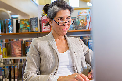 Older Hispanic woman using computer in library - p555m1414256 by Marc Romanelli