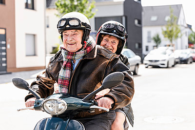 Happy senior couple riding motor scooter - p300m2030394 by Uwe Umstätter