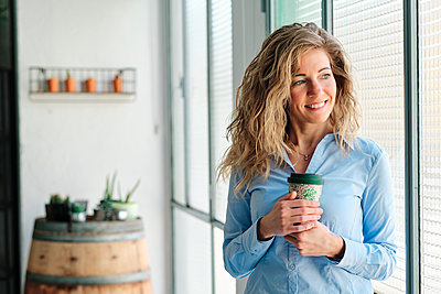 Smiling blond woman with reusable cup looking through window - p300m2264561 by Alvaro Gonzalez