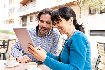 Man and woman using digital tablet at terrace - p300m2282148 by Jose Carlos Ichiro