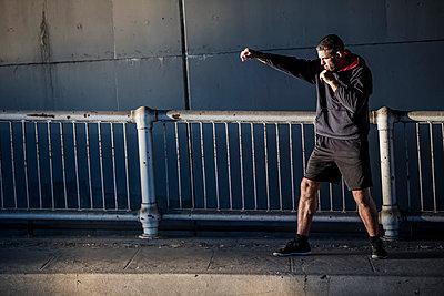 Caucasian man shadow boxing near railing - p555m1472982 by Richard Seagraves