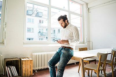 Junger Mann benutzt eine Smartphone App - p586m1511234 von Kniel Synnatzschke