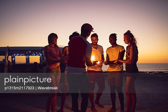 Friends lighting sparklers near cameraman during sunset - p1315m2117923 by Wavebreak