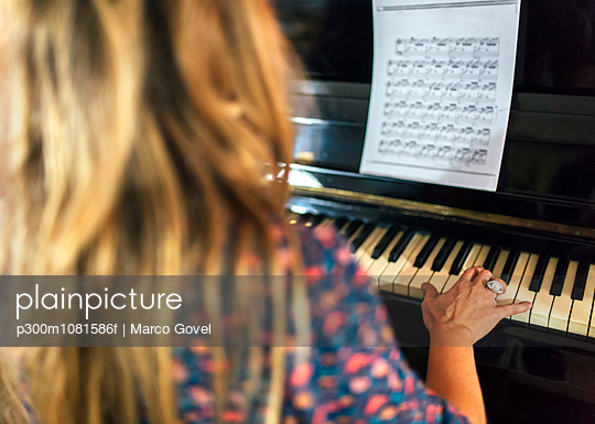 Woman playing piano - p300m1081586f by Marco Govel