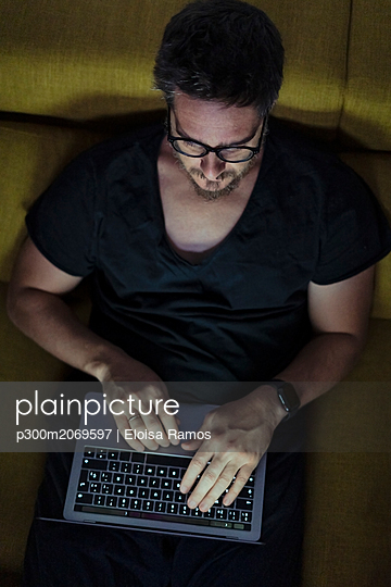 Man sitting on couch using laptop at night - p300m2069597 by Eloisa Ramos
