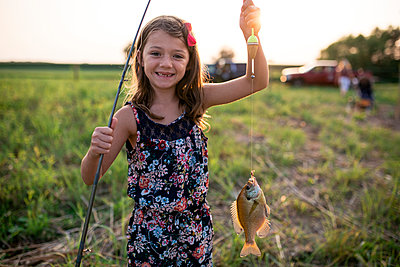 Portrait of smiling girl holding dead fish in fishing line on field during sunset - p1166m2040003 by Cavan Images