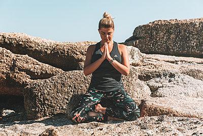 Junge Frau meditiert auf dem Strand - p1640m2261153 von Holly & John