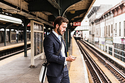 Young businessman waiting at metro station platform, using smart phone - p300m1191900 by Uwe Umstätter