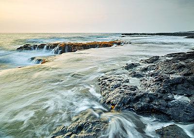 Waves splashing on volcanic rocks in Kealakekua Bay against sky during sunset - p300m2131768 by Christian Vorhofer
