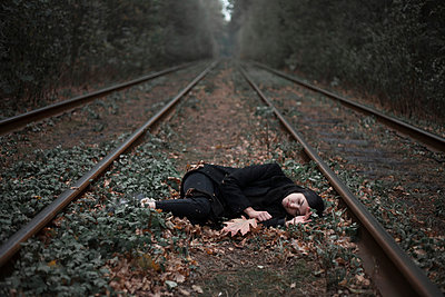 Caucasian woman laying on autumn leaves near train tracks in forest - p555m1491519 by Dmitriy Bilous