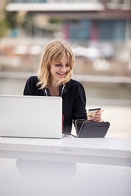 Junge Frau am Laptop Computer mit Kreditkarte - p788m1466118 von Lisa Krechting