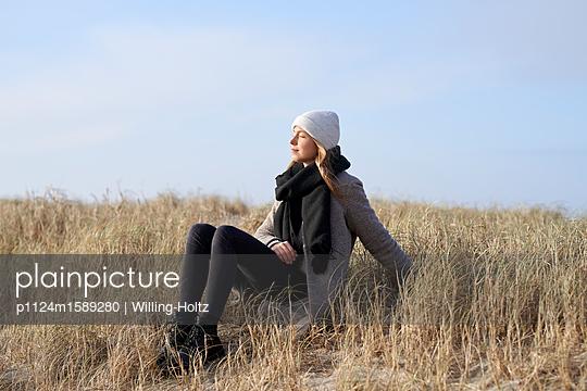 Frau sitzt in den Dünen - p1124m1589280 von Willing-Holtz