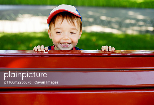 Cute toddler smiling happily peeking out from behind red park bench - p1166m2250678 by Cavan Images