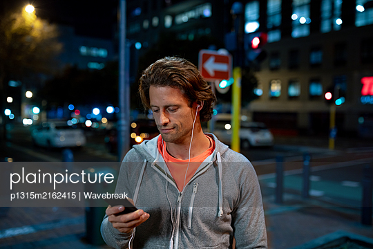 Young man using smartphone - p1315m2162415 by Wavebreak