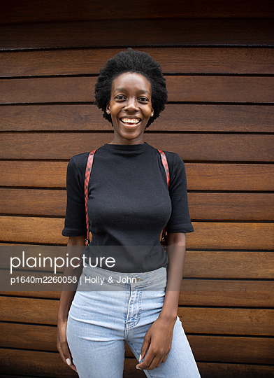 Young african woman in front of a wooden wall, portrait - p1640m2260058 by Holly & John