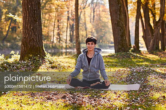 Mid adult woman practicing yoga at canal - p300m1581472 von Stefan Hobmaier