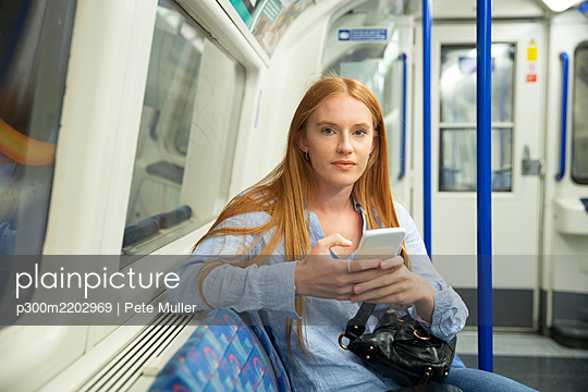 Beautiful woman holding smart phone while sitting in train - p300m2202969 by Pete Muller