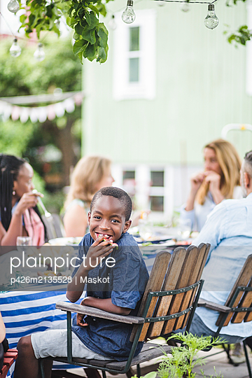 Smiling boy eating watermelon while sitting with family in garden party - p426m2135528 by Maskot