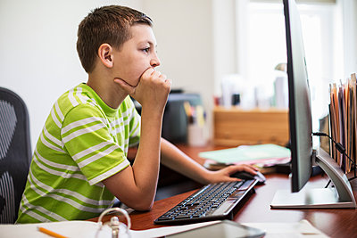 Young Caucasian boy at work on a desk top computer system. - p1100m1554042 by Mint Images