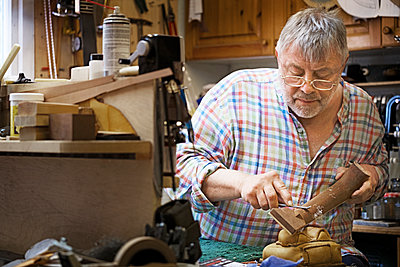 Concentrated man shaping fretboard in workshop - p1166m1163573 by Cavan Images