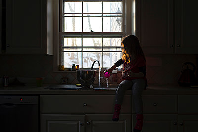 Girl playing with water while sitting at kitchen sink - p1166m1423385 by Cavan Images
