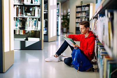 Man studying while sitting on floor at library - p1166m1530416 by Cavan Images