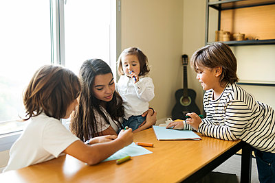 Nanny baby sitting  siblings and doing home work at home - p1166m2084995 by Cavan Images
