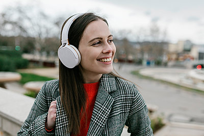 Young woman with headphones while looking away in city - p300m2268319 by Xavier Lorenzo